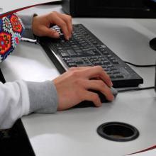 Manos de alumna sobre el teclado utilizando el portal del CUCIÉNEGA